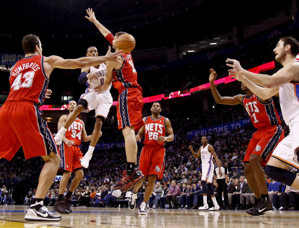 Oklahoma City's Russell Westbrook passes the ball past New Jersey's Brook Lopez to Nenad Krstic during the NBA basketball game between the Oklahoma City Thunder and the New Jersey Nets at the Oklahoma City Arena, Wednesday, Dec. 29, 2010.  Photo by Bryan Terry, The Oklahoman