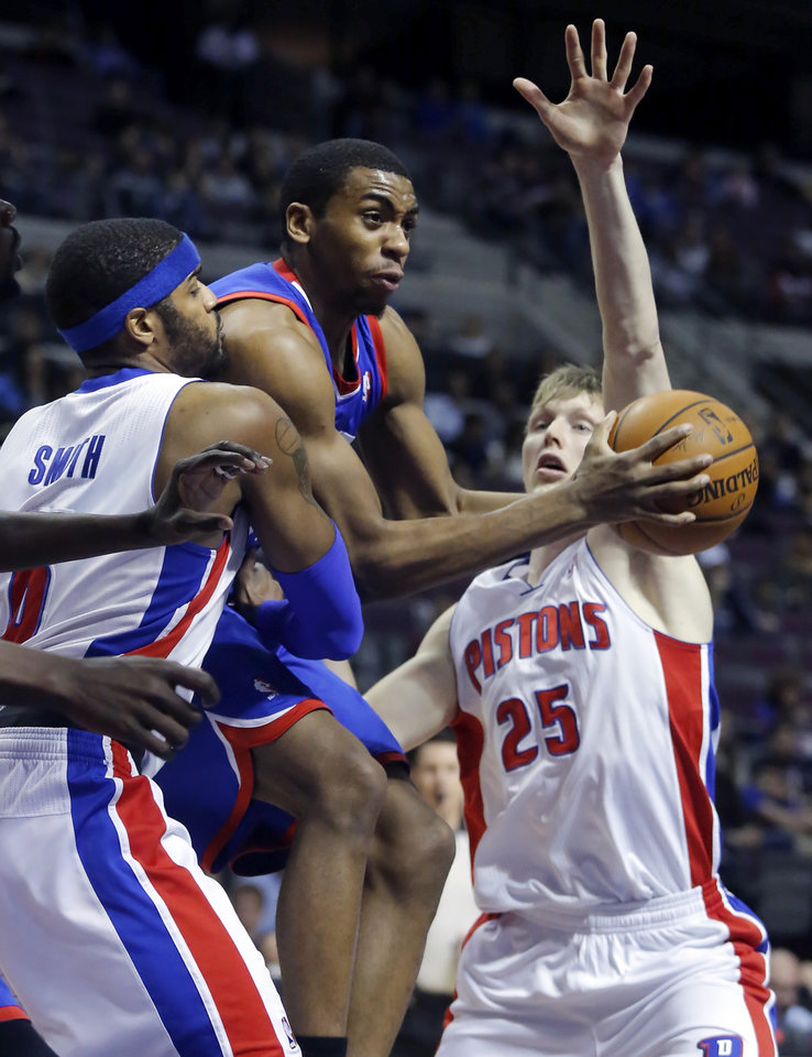 Photo - Philadelphia 76ers forward Hollis Thompson, center, is forced to pass the ball as he splits the defense of Detroit Pistons forward Josh Smith (6) and guard Kyle Singler (25) during the first half of an NBA basketball game, Saturday, Feb. 1, 2014, in Auburn Hills, Mich. (AP Photo/Duane Burleson)