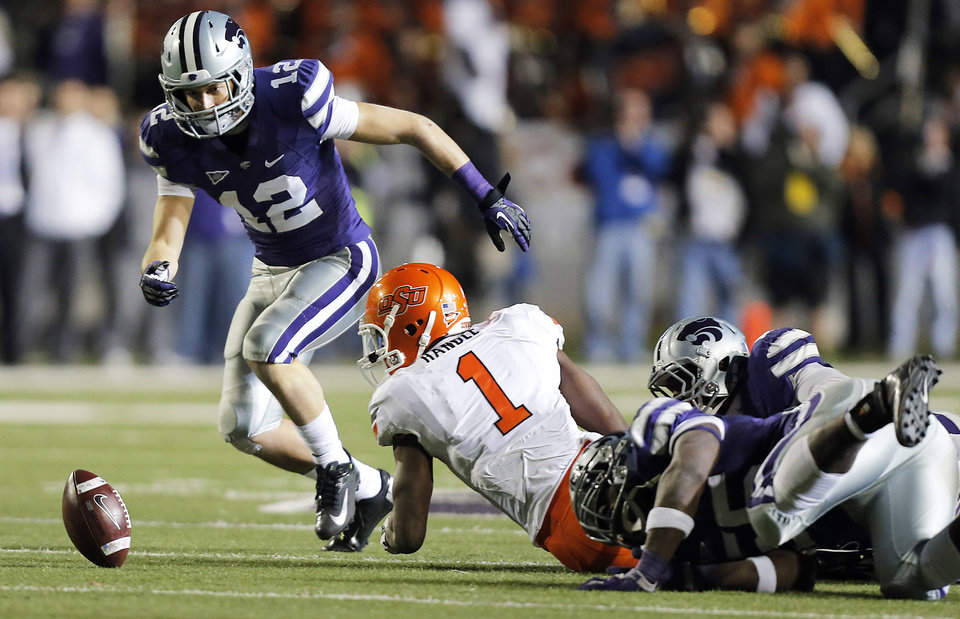 Photo - Oklahoma State's Joseph Randle, center, fumbles the ball as Kansas State's Ty Zimmerman, left, looks to recover during Saturday's game in Manhattan, Kan. Russell had 15 carries for 43 yards.Photo by Chris Landsberger, The Oklahoman