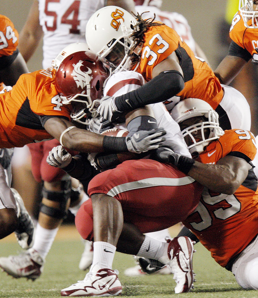 Photo - OSU's Justin Gilbert (4), LeRon Furr (33) and Richetti Jones (99) stop WSU's Logwone Mitz for a three-yard during the college football game between the Washington State Cougars (WSU) and the Oklahoma State Cowboys (OSU) at Boone Pickens Stadium in Stillwater, Okla., Saturday, September 4, 2010. OSU won, 65-17. Photo by Nate Billings, The Oklahoman