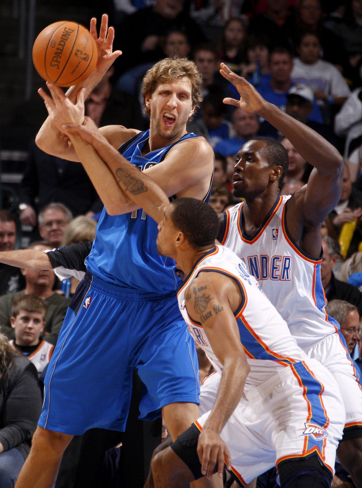 Photo - Oklahoma City's' Thabo Sefolosha (2) and Serge Ibaka (9) defend Dallas' Dirk Nowitzki (41) during a preseason NBA game between the Oklahoma City Thunder and the Dallas Mavericks at Chesapeake Energy Arena in Oklahoma City, Tuesday, Dec. 20, 2011. Photo by Bryan Terry, The Oklahoman