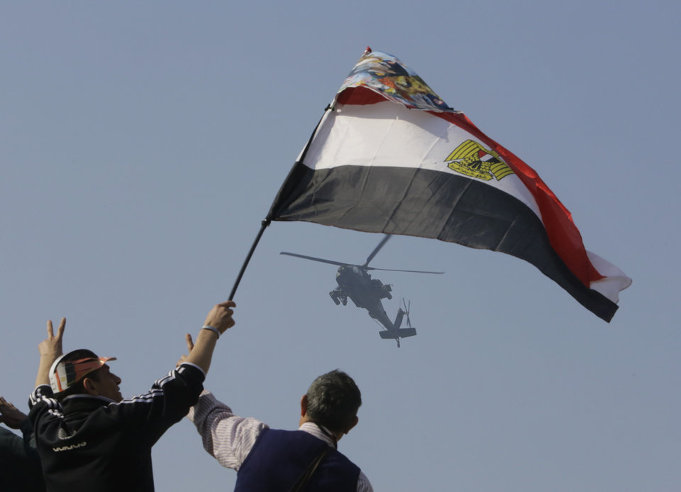 Photo - Egyptians wave a national flag as they greet an army helicopter flying over Tahrir Square, the epicenter of the 2011 uprising, in Cairo, Egypt, Saturday, Jan. 25, 2014. As Egyptians mark the third anniversary of their spectacular revolt against autocrat Hosni Mubarak in the name of democracy on Saturday, there has been a powerful sign of the country's stunning reversals since: letters of despair by some of the prominent activists who helped lead the uprising, leaked from the prisons where they are now jailed. (AP Photo/Amr Nabil)