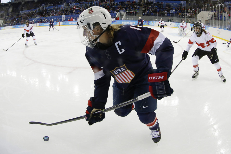 Photo - Meghan Duggan of the Untied States talks control of the puck as Evelina Raselli of Switzerland chases her during the third period of the 2014 Winter Olympics women's ice hockey game at Shayba Arena, Monday, Feb. 10, 2014, in Sochi, Russia. (AP Photo/Matt Slocum)