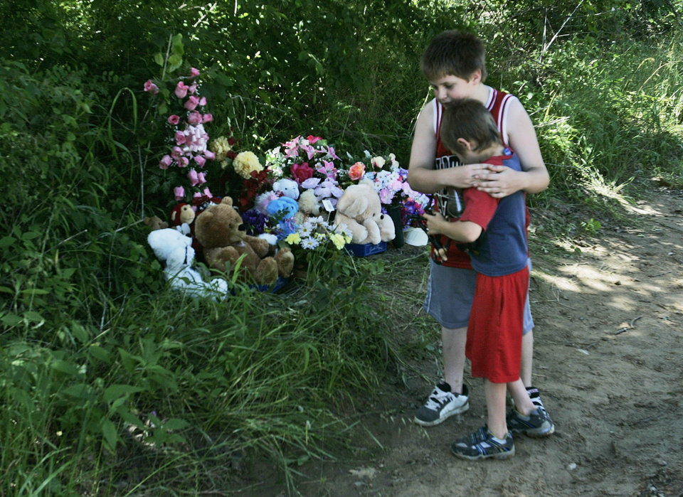 Photo - MURDERS, SHOOTING DEATHS, GIRLS, TAYLOR PLACKER, TAYLOR DAWN PASCHAL-PLACKER , SKYLA JADE WHITAKER, WELEETKA: Dakota Padgett, 10, hugs his brother, Devon Padgett, 7, in front of a memorial on the side of the road for Skyla Whitaker, 11, and Taylor Paschal-Placker, 13, on Wednesday, June 11, 2008. The two girls were found murdered Sunday night. (AP Photo) ORG XMIT: OKSO108