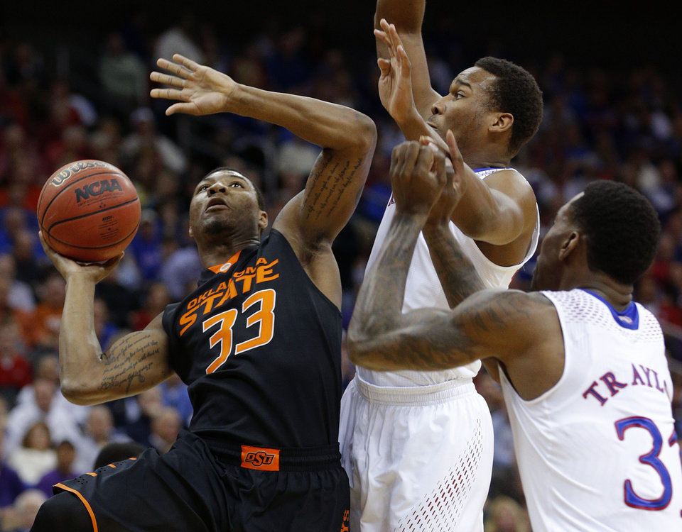 Photo - Oklahoma State's Marcus Smart (33) tries to get past Kansas' Wayne Selden, Jr. (1) and Jamari Traylor (31) during the Big 12 Tournament college basketball game between Oklahoma State University and Kansas at the Sprint Center in Kansas City, Mo., Thursday, March 13, 2014. Kansas won 77-70. Photo by Bryan Terry, The Oklahoman