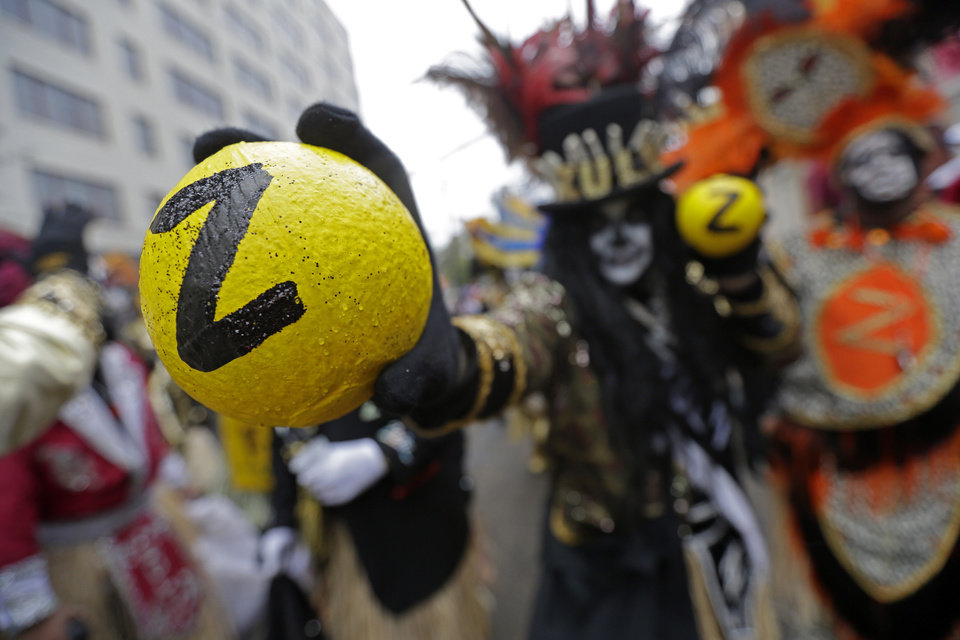 Photo - Members of the Krewe of Zulu hold painted coconuts to give to parade-goers, as they march during Mardi Gras day in New Orleans, Tuesday, March 4, 2014.  Despite rain and cold in Tuesday's forecast, revelers are gathering along parade routes as the Carnival season in New Orleans heads to a crest with the unabashed celebration of Mardi Gras. The Zulu parade began on schedule, led by a New Orleans police vanguard on horseback that included Mayor Mitch Landrieu. (AP Photo/Gerald Herbert)