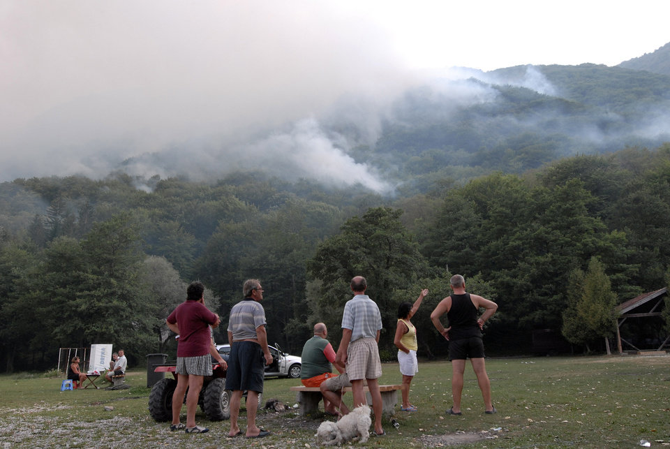 Bosnians watch a forest fire at Boracko Lake near the town of Konjic, 50 km south of Sarajevo in Bosnia, Tuesday Aug. 21. 2012. Citizens and tourists began evacuating from Boracko Lake as wildfires reached the houses and tourist camps in the area. (AP Photo/Sulejman Omerbasic)