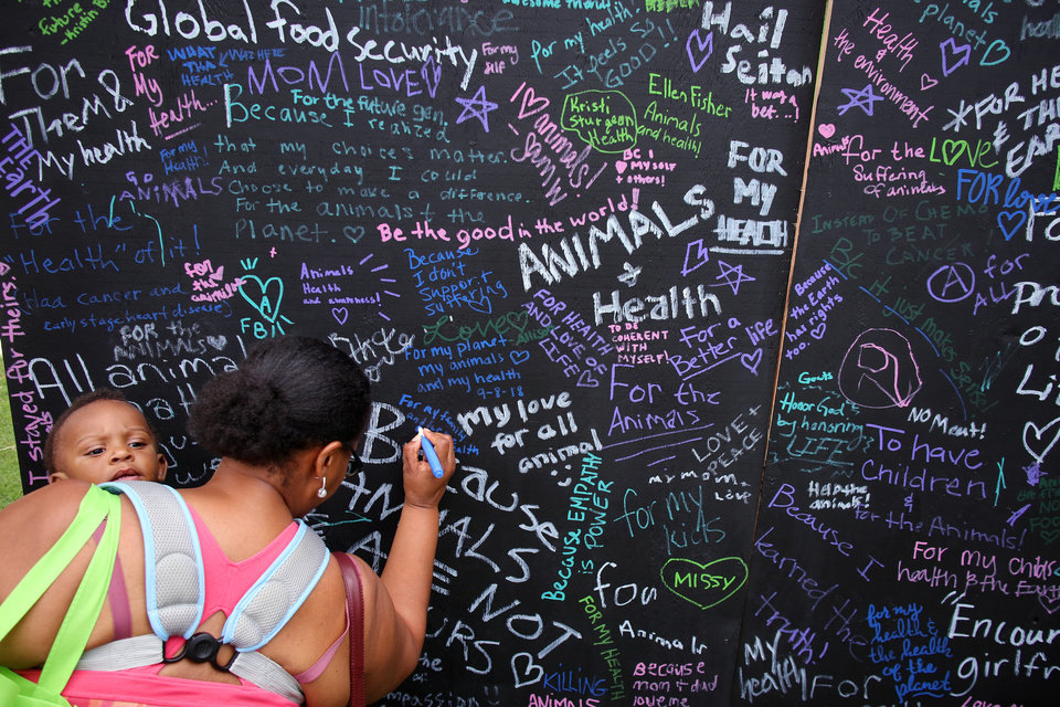 Photo -  Erika Dangerfield writes Saturday on a display board at VegFest why she became a vegan as she holds her grandson, Zaiden Nunn, 11 months. [PHOTO BY DOUG HOKE, THE OKLAHOMAN]