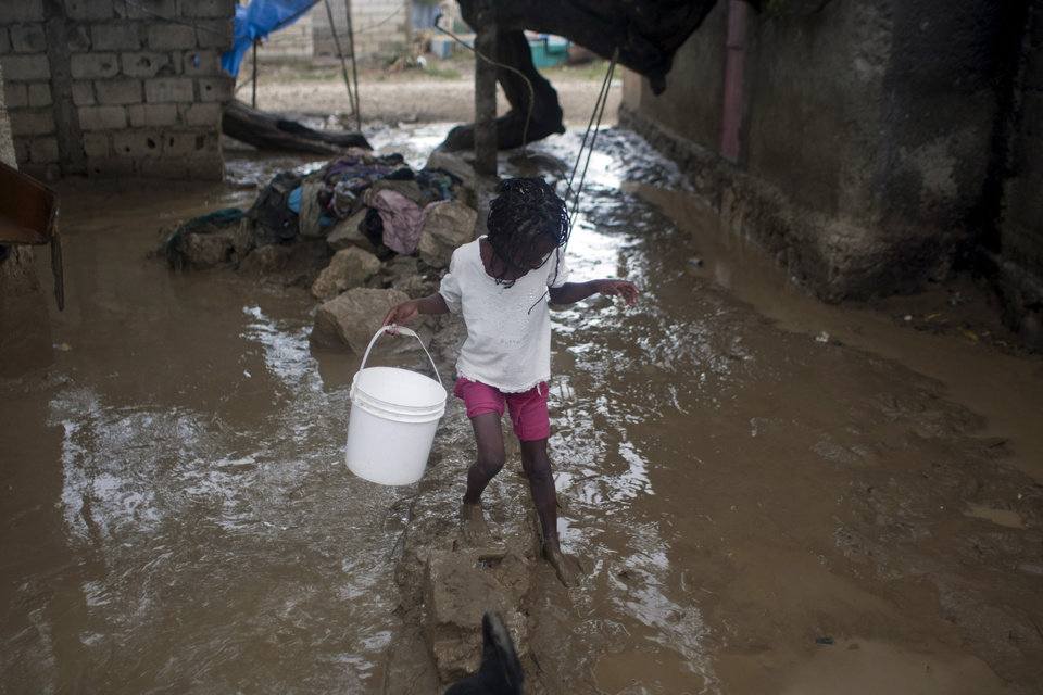 A girl carries a bucket at her flooded home after the passing of Tropical Storm Isaac in Port-au-Prince, Haiti, Sunday Aug. 26, 2012. The death toll in Haiti from Tropical Storm Isaac has climbed to seven after an initial report of four deaths, the Haitian government said Sunday. (AP Photo/Dieu Nalio Chery) ORG XMIT: PAP104