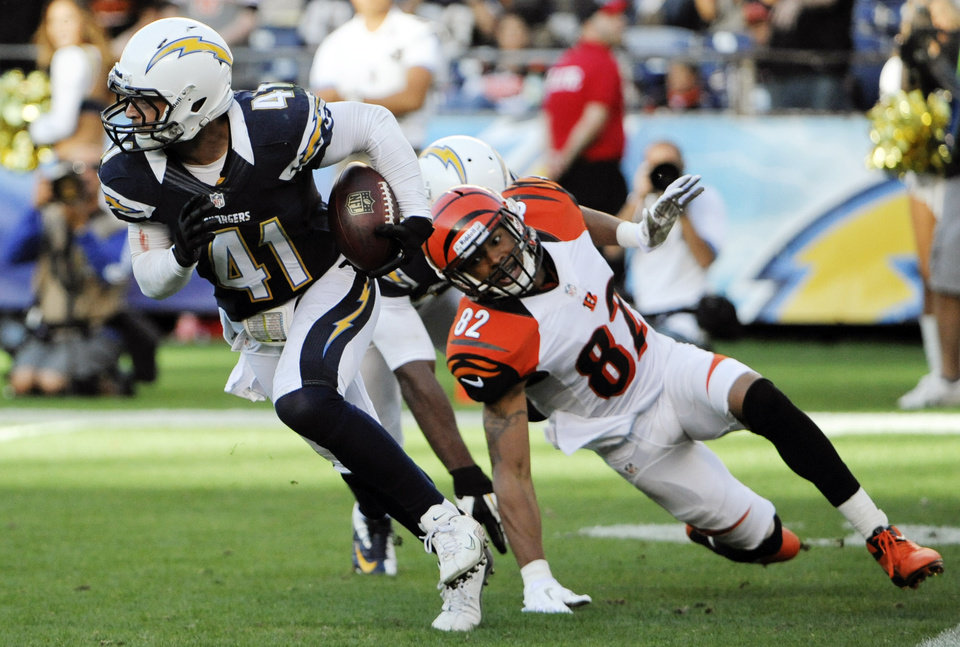 Photo - San Diego Chargers defensive back Corey Lynch (41) runs upfield after grabbing an interception as Cincinnati Bengals wide receiver Marvin Jones, right, watches during the second half of an NFL football game, Sunday, Dec. 2, 2012, in San Diego. (AP Photo/Denis Poroy)