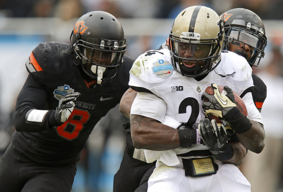 Photo - Oklahoma State's Daytawion Lowe (8) and Justin Gilbert (4) bring down Purdue's Akeem Shavers (24) during the Heart of Dallas Bowl football game between Oklahoma State University and Purdue University at the Cotton Bowl in Dallas, Tuesday, Jan. 1, 2013. Oklahoma State won 58-14. Photo by Bryan Terry, The Oklahoman