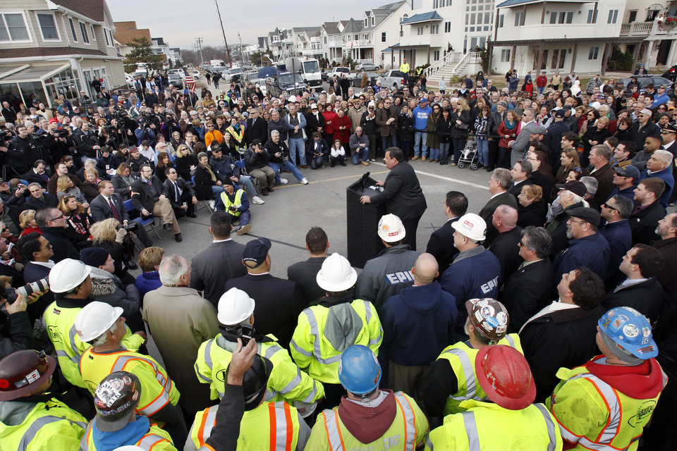 Photo - Gov. Chris Christie, center, addresses a large gathering, including construction workers, Wednesday, Jan. 9, 2013, in Belmar, N.J., as he helps officials kick off the construction on a 1.3-mile section of  boardwalk to replace the walkway destroyed by Superstorm Sandy in October. The goal is to have it done by May. (AP Photo/Mel Evans)