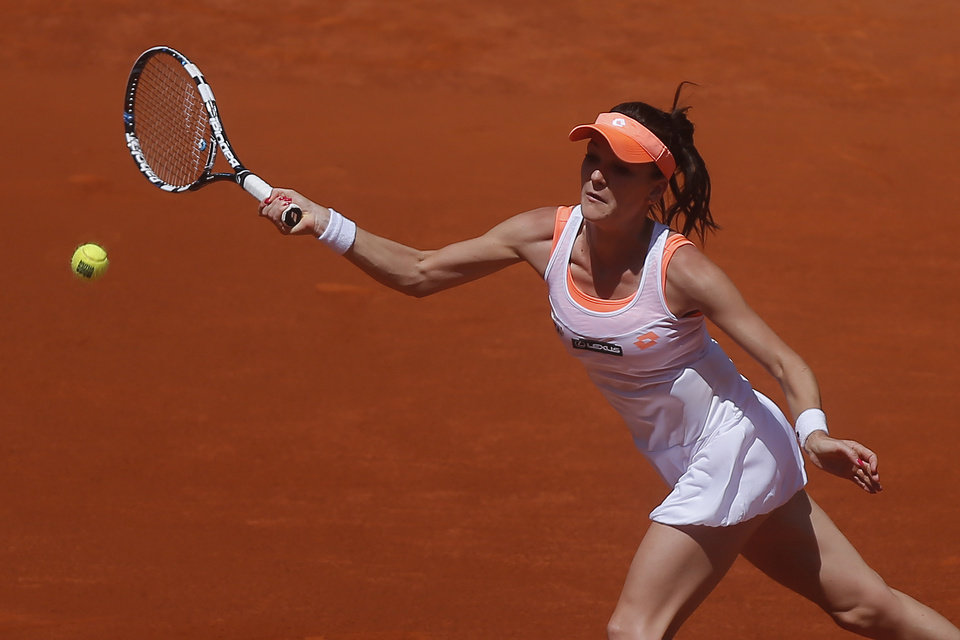 Photo - Agnieszka Radwanska from Poland returns the ball during a Madrid Open tennis tournament match against Eugenie Bouchard from Canada, in Madrid, Spain, Monday, May 5, 2014. (AP Photo/Andres Kudacki)