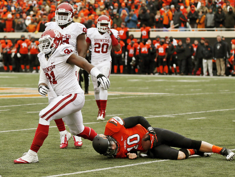 Photo - Oklahoma's Charles Tapper (91) reacts after sacking Oklahoma State's Clint Chelf (10) on the second to last play of the game in front of Oklahoma's Chuka Ndulue (98) and Frank Shannon (20) in the fourth quarter of the Bedlam college football game between the Oklahoma State University Cowboys (OSU) and the University of Oklahoma Sooners (OU) at Boone Pickens Stadium in Stillwater, Okla., Saturday, Dec. 7, 2013. OU won, 33-24. Photo by Nate Billings, The Oklahoman