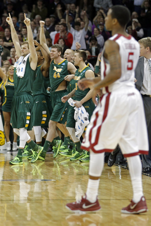 Photo - The North Dakota State bench celebrates their win in front of Oklahoma's Je'lon Hornbeak (5) during the NCAA men's basketball tournament game between the University of Oklahoma and North Dakota State at the Spokane Arena in Spokane, Wash., Thursday, March 20, 2014. Oklahoma home lost 80-75. Photo by Sarah Phipps, The Oklahoman