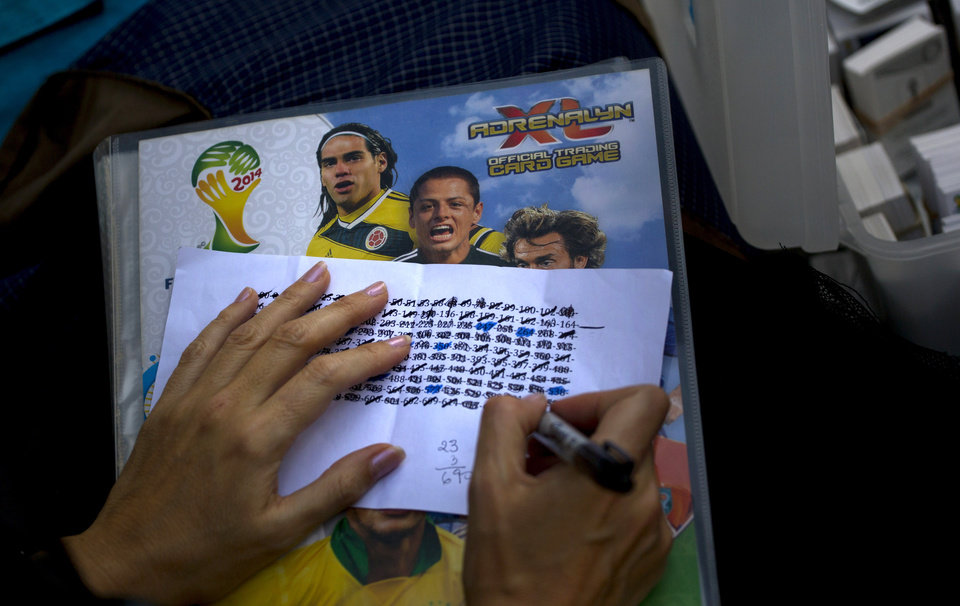Photo - A woman marks the numbers she needs to complete World Cup sticker album at a meeting of collectors in Caracas, Venezuela, Saturday, June 21, 2014. Venezuela is again sitting out the World Cup, but many people here have been swept up in a related competition: the race to complete their World Cup sticker albums. Adults and children alike are spilling into plazas around the country to swap and buy business card-sized stickers with the faces of players and photos of Brazilian stadiums.  (AP Photo/Ramon Espinosa)