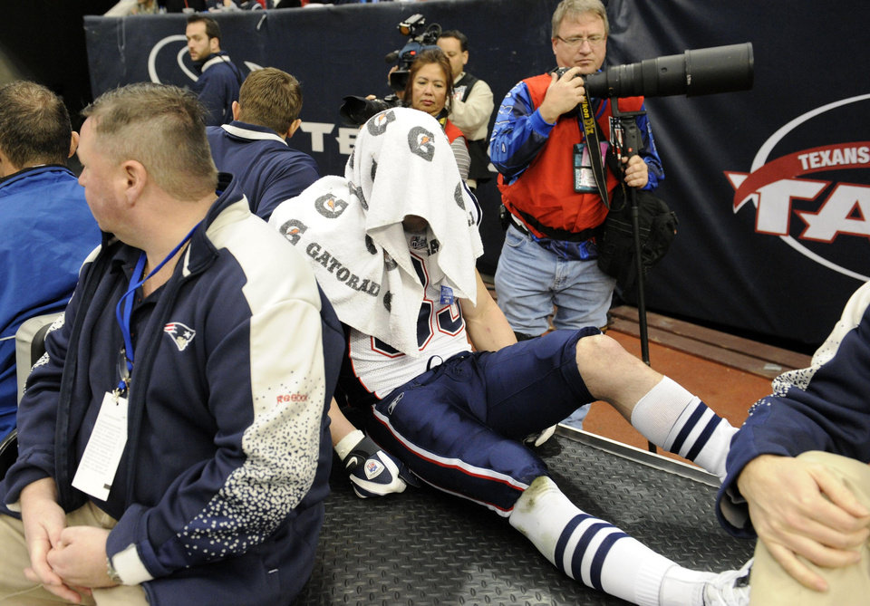Photo - KNEE INJURY / INJURED: New England Patriots wide receiver Wes Welker, center, is driven off the field after catching a pass and being tackled during the first quarter of an NFL football game against the Houston Texans, Sunday, Jan. 3, 2010, in Houston. (AP Photo/Dave Einsel) ORG XMIT: HTT109