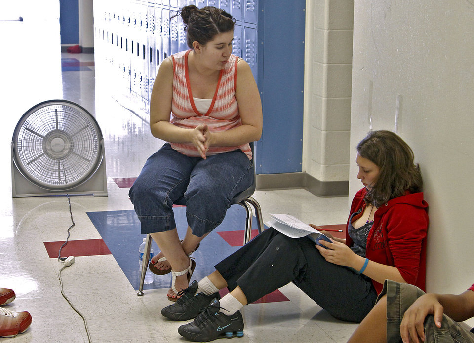 Photo - HEAT / HOT WEATHER: John Marshall High School math teacher Cassi Yarbrough works with student in front of a fan as she teaches her class in the hallway to help keep the students cooler while there was no air conditioning at John Marshall High School on Friday, March 30 2012, in Oklahoma City, Oklahoma.  Photo by Chris Landsberger, The Oklahoman