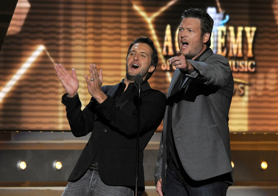 Photo - FILE - In this April 7, 2013 file photo, Luke Bryan, left, and Blake Shelton speak on stage at the 48th Annual Academy of Country Music Awards at the MGM Grand Garden Arena in Las Vegas. The 2014 Academy of Country Music Awards in Las Vegas will air live Sunday night, April 6, 2014, from 8-11 p.m. EDT on CBS. Several awards, including top honor entertainer of the year, will be announced during the broadcast, to be hosted by Blake Shelton and Luke Bryan. Shelton, Bryan, George Strait, Miranda Lambert, Jason Aldean, Keith Urban, Tim McGraw, Shakira and Stevie Nicks are scheduled to perform. (Photo by Chris Pizzello/Invision/AP, File)