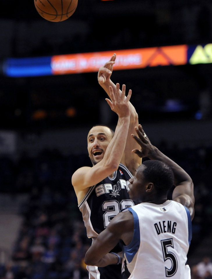 Photo - San Antonio Spurs' Tiago Splitter, from Brazil, passes over Minnesota Timberwolves' Gorgui Dieng (5) during the second quarter in an NBA basketball game at the Target Center in Minneapolis on Tuesday, April 8, 2014. (AP Photo/Hannah Foslien)