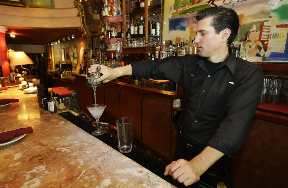 Photo - In this June 2, 2014 photo, Gradie Wallen a bartender at the icon Grill in Seattle, mixes a drink as he works during lunchtime. An Associated Press comparison of the cost of living at several other major U.S. cities found that a $15 minimum wage, like Seattle adopted this week, will make a difference, but won't buy a lavish lifestyle. (AP Photo/Ted S. Warren)