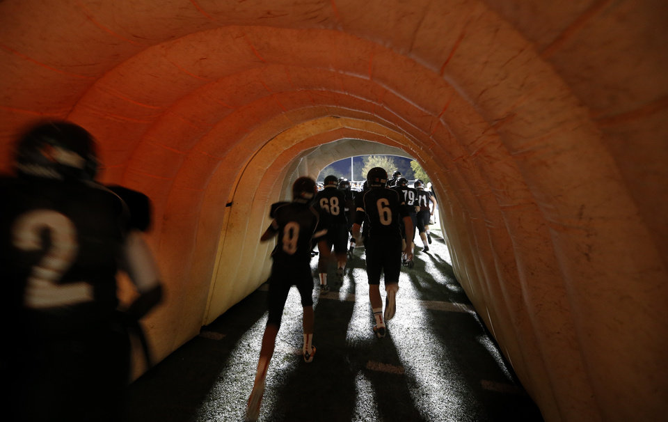 Photo - Norman players run on to the field before the high school football game between Norman and Yukon at Norman High School in Norman, Okla., Thursday, Nov. 8, 2012. Photo by Sarah Phipps, The Oklahoman