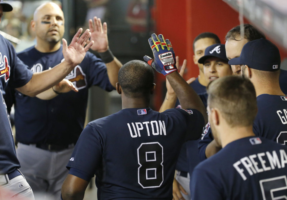 Photo - Atlanta Braves' Justin Upton (8) is congratulated in the dugout by teammates after hitting a two run home run against the Arizona Diamondbacks during the sixth inning of a baseball game, Sunday, June 8, 2014, in Phoenix. (AP Photo/Matt York)