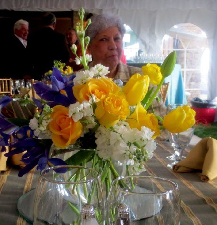 Maggie Barrett peeks through the flowers at the party that Jose Freede and daughters, Cathy Freede, and Margaret Owens, hosted for a recent Symphony Show House Evening at �The Trio in the Abbey�.  The guests were in The Contemporary House in The Abbey Café where a tent was set up, complete with chandeliers.  Bouquets of blue iris, yellow and orange roses and white hydrangeas decorated the tables and tall vases with the same flowers plus calla lilies were on the buffet table where tenderloin and shrimp were served, along with a separate table of various desserts such as chocolate mousse, tarts and cake. (Photo by Helen Ford Wallace).