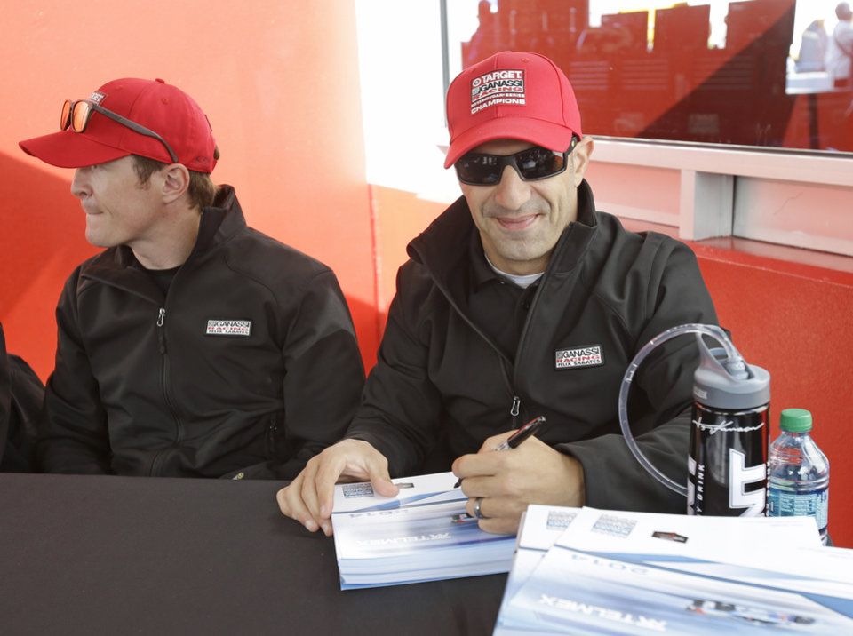 Photo - Scott Dixon, left, of New Zealand, and Tony Kanaan, of Brazil, signs autographs for fans prior to the start of the IMSA Series Rolex 24 hour auto race at Daytona International Speedway in Daytona Beach, Fla., Saturday, Jan. 25, 2014.(AP Photo/John Raoux)
