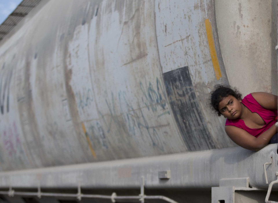 Photo - In this Saturday, July 12, 2014 photo, a young migrant girl waits for a freight train to depart on her way to the U.S. border, in Ixtepec, Mexico. Immigrants' rights advocates in the U.S. say they are seeing more children from Central America who are not only fleeing gang recruitment and random violence, but who have been targeted themselves. (AP Photo/Eduardo Verdugo)