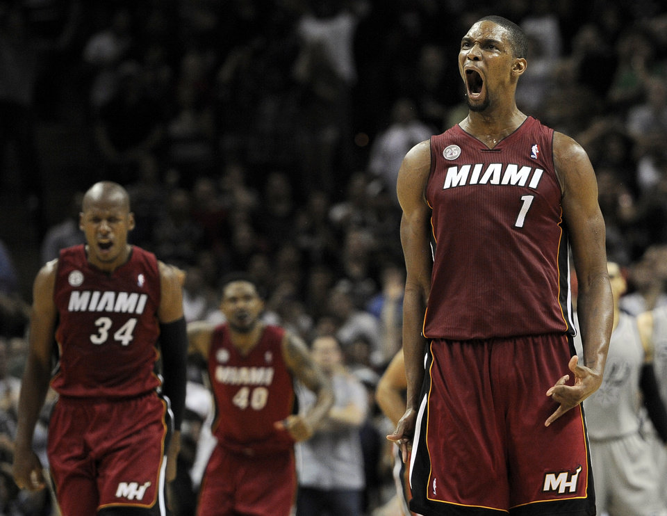 Photo - Miami Heat's Chris Bosh (1) yells after scoring the winning 3-pointer with 1.9 seconds left in an NBA basketball game against the San Antonio Spurs, Sunday, March 31, 2013, in San Antonio. Ray Allen (34) and Udonis Haslem (40) also celebrate the play. Bosh scored 23 points as Miami won 88-86. (AP Photo/Darren Abate)
