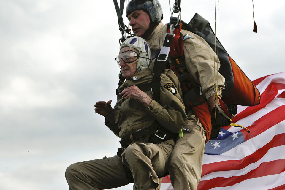 Photo - 93 year old U.S WW II veteran Jim Martin of the 101st Airborne, left, completes a tandem parachute jump onto Utah Beach, western France, Thursday June 5, 2014, as part of the commemoration of the 70th anniversary of the D Day. World leaders and veterans prepare to mark the 70th anniversary of the invasion this week in Normandy. (AP Photo/Thibault Camus)