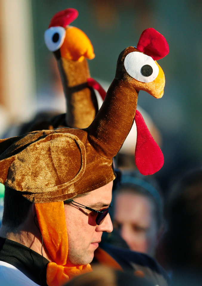 Photo - Family members Justin Lowry, Philip Lowry and Josh Martin wear turkey-head hats as they wait with other participants for the start of the 5K run  during the annual Turkey Trot in downtown Edmond Thursday morning,  Nov. 24, 2011.   Photo by Jim Beckel, The Oklahoman
