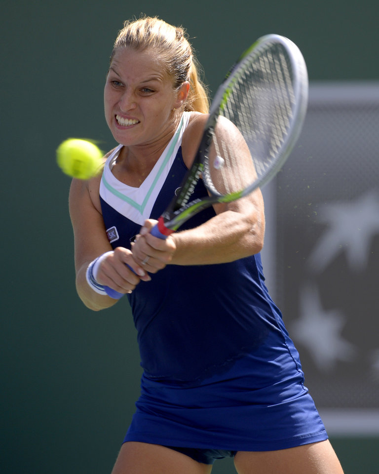 Photo - Dominika Cibulkova, of Slovakia, returns a shot to Li Na, of China, during a quarterfinal match at the BNP Paribas Open tennis tournament, Thursday, March 13, 2014 in Indian Wells, Calif. (AP Photo/Mark J. Terrill)