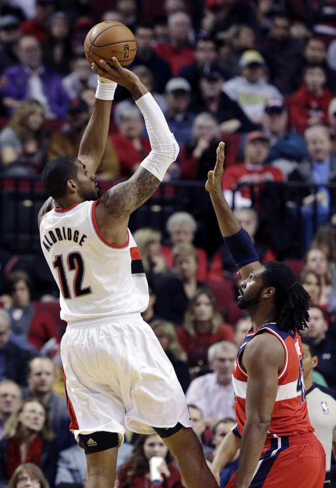 Photo - Portland Trail Blazers forward LaMarcus Aldridge shoots over Washington Wizards forward Nene during the first quarter of an NBA basketball game in Portland, Ore., Monday, Jan. 21, 2013.(AP Photo/Don Ryan)