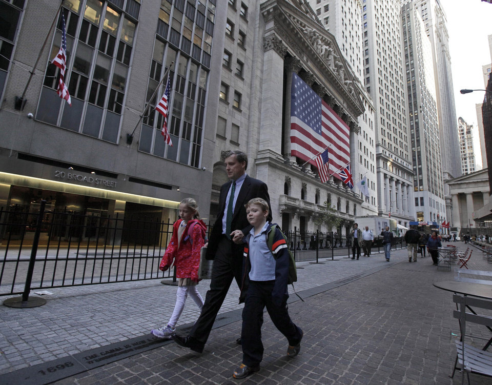 Photo -   A man with two children passes the New York Stock Exchange, Thursday morning, Oct. 18, 2012. A Bangladeshi man, 21-year-old Quazi Mohammad Rezwanul Ahsan Nafis, snared in an FBI terror sting, considered targeting a high-ranking government official and the New York Stock Exchange before authorities say he raised the bar further by picking one of New York City's most fortified sites: The Federal Reserve. (AP Photo/Richard Drew)