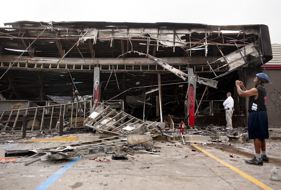 Photo - Passers-by and media take a closer look Monday, Aug. 11, 2014 at the burned-out shell of the QuikTrip gas station torched during the violence that erupted in Ferguson, Mo. overnight following a candle-light memorial for 18-year-old shooting victim Michael Brown. Police said Brown, who was unarmed, was fatally shot Saturday in a scuffle with an officer.  (AP Photo/Sid Hastings)