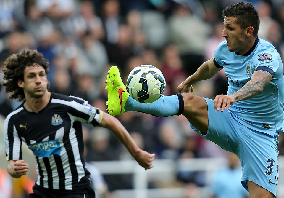 Photo - Manchester City's Steven Jovetic, right, vies for the ball with Newcastle United's captain Fabricio Coloccini, left, during their English Premier League soccer match at St James' Park, Newcastle, England, Sunday, Aug. 17, 2014. (AP Photo/Scott Heppell)
