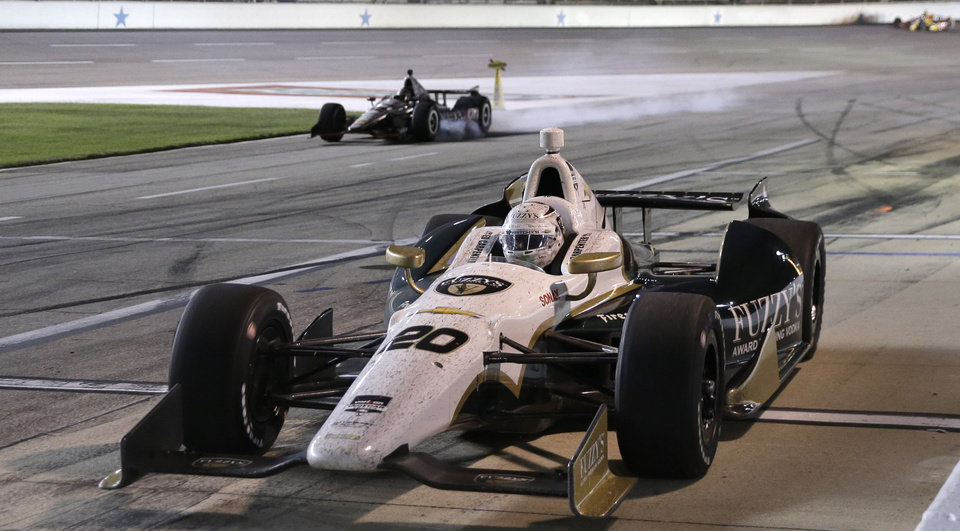 Photo - Ed Carpenter (20) pulls in for a pit stop as Will Power, of Australia, locks up his tires while slowing in the background during the IndyCar auto race at Texas Motor Speedway in Fort Worth, Texas, Saturday, June 7, 2014. Power was penalized for speeding on pit row. (AP Photo/Tim Sharp)