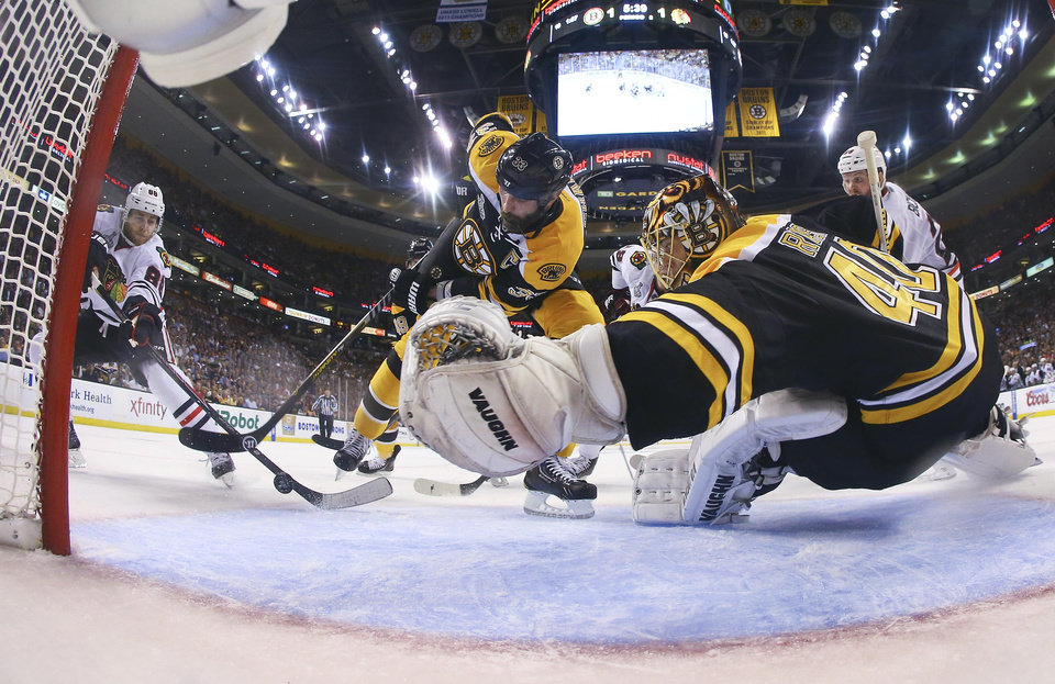 Photo - Boston Bruins defenseman Zdeno Chara (33), of Slovakia, turns the puck from the net in front of Boston Bruins goalie Tuukka Rask, right, of Finland, as Chicago Blackhawks right wing Patrick Kane, left, moves in during the second period in Game 6 of the NHL hockey Stanley Cup Finals Monday, June 24, 2013, in Boston. (AP Photo/Harry How, Pool)