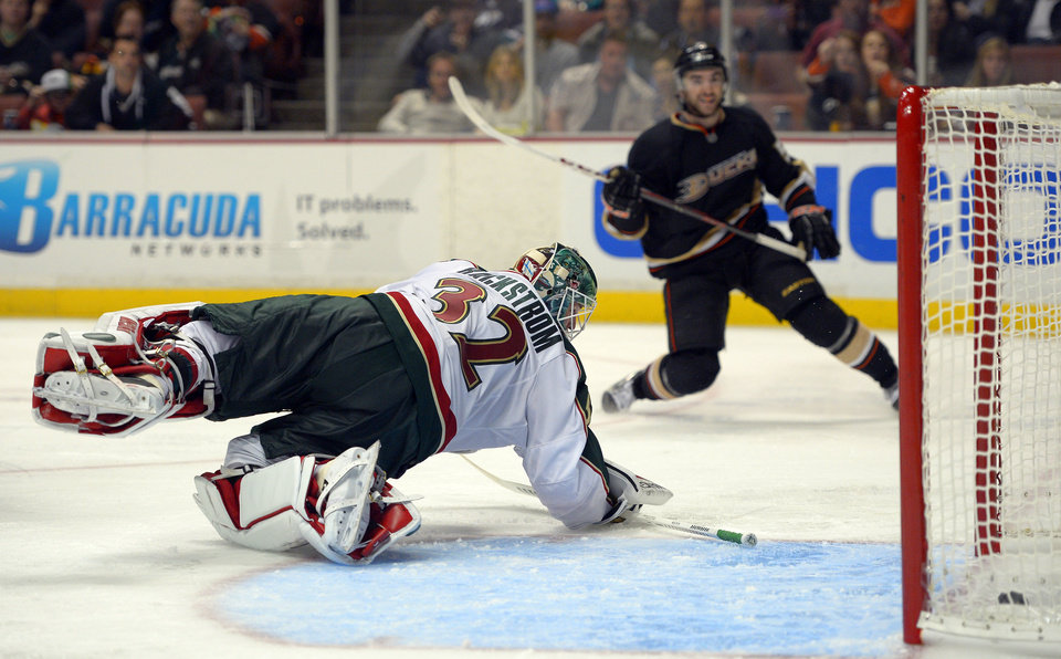 Photo - Anaheim Ducks right wing Kyle Palmieri, right, scores on Minnesota Wild goalie Niklas Backstrom during the second period of an NHL hockey game, Friday, Feb. 1, 2013, in Anaheim, Calif. (AP Photo/Mark J. Terrill)