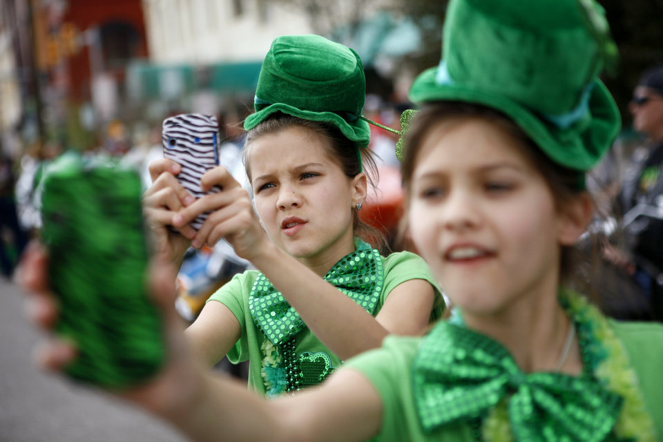 Corra VanHoozer, 11, at left, and her sister, Caitlynn, 11, take photos during the annual St. Patrick's Day Parade in downtown Oklahoma City, Saturday, March 17, 2012. Photo by Bryan Terry, The Oklahoman