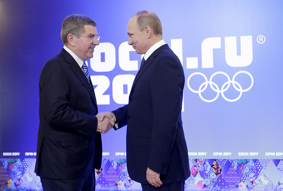 Photo - Russian President Vladimir Putin, right, greets International Olympic Committee President Thomas Bach at an event welcoming IOC members ahead of the upcoming 2014 Winter Olympics at the Rus Hotel, Tuesday, Feb. 4, 2014, in Sochi, Russia. (AP Photo/David Goldman, Pool)