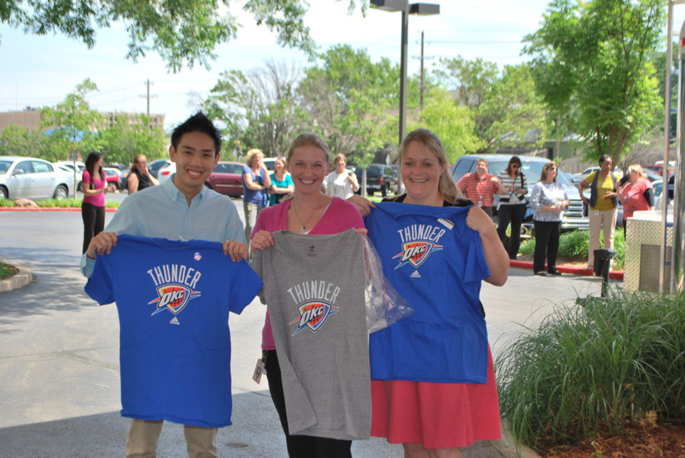 Photo - American Fidelity Assurance colleagues, from left, Peter Tran, Summer Morley and Carrie Voden show off their newly purchased Thunder gear. PHOTO PROVIDED