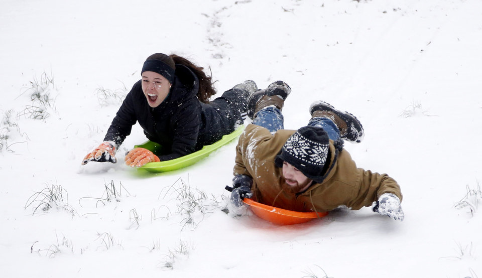 Photo - Austin Carter, right, sled races Isabelle Pommier down the hills in Avent  Park, Friday in Oxford, Miss., Jan. 22, 2016. The two Mississippi students took advantage of the university being closed to sled on the hills along with several dozen people. The two inches of accumulated power was enough for many families who trekked to the park to take advantage of the long gentle slopes for their children to slide down. Although the snow ceased falling, temperatures are expected to drop in the afternoon making for hazardous driving in north Mississippi. (AP Photo/Rogelio V. Solis)