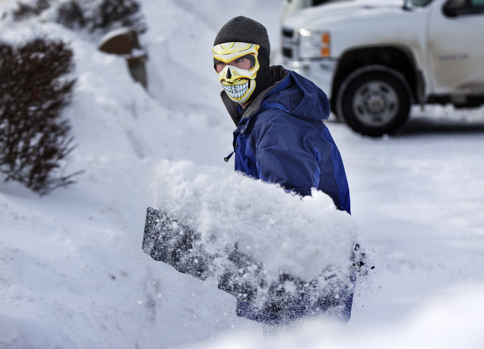 Photo - With the temperature a frightful 3 degrees Fahrenheit, Drue Ford shovels snow wearing a face mask to guard against frostbite, Friday, Jan. 3, 2014, in Brunswick, Maine. (AP Photo/Robert F. Bukaty)