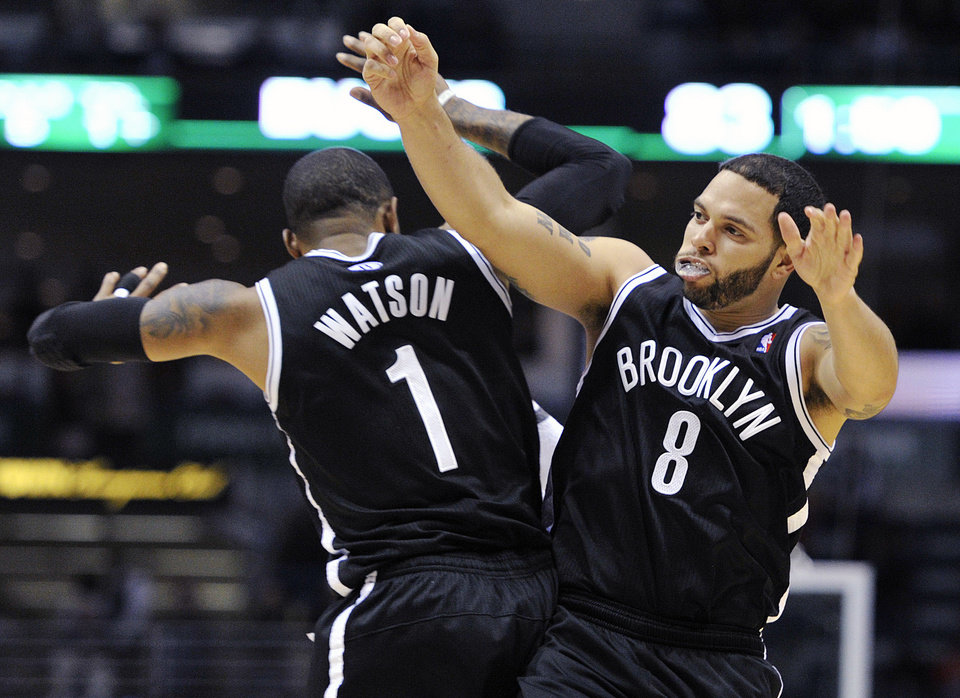 Brooklyn Nets' C.J. Watson (1) celebrates with Deron Williams (8) after Williams' late basket against the Milwaukee Bucks during the second half of an NBA basketball game, Wednesday, Feb. 20, 2013, in Milwaukee. The Nets won 97-94. (AP Photo/Jim Prisching)