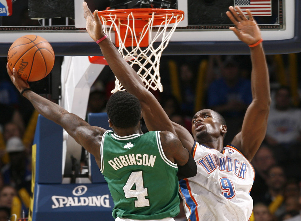 Photo - Oklahoma City's Serge Ibaka defends against Nate Robinson during the NBA basketball game between the Oklahoma City Thunder and the Boston Celtics, Sunday, Nov. 7, 2010, at the Oklahoma City Arena. Photo by Sarah Phipps, The Oklahoman