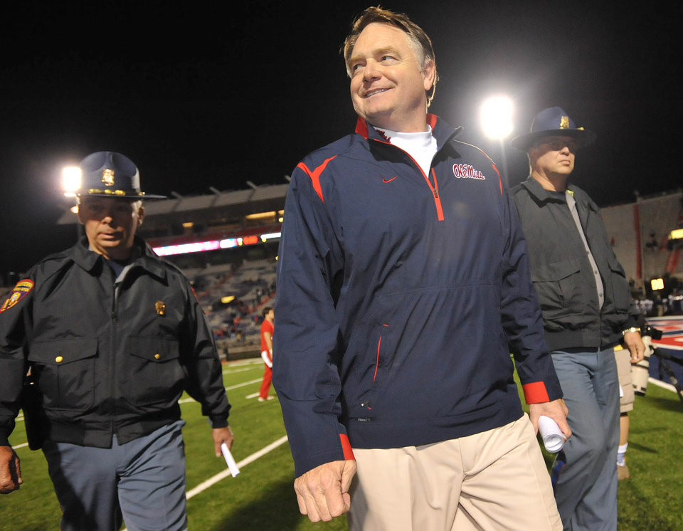 Photo - Mississippi head coach Houston Nutt, foreground, smiles as he is escorted off the field after their NCAA college football game against Northern Arizona in Oxford, Miss., Saturday, Nov. 7, 2009. (AP Photo/The Clarion-Ledger,Ryan Moore) ORG XMIT: MSJAD103