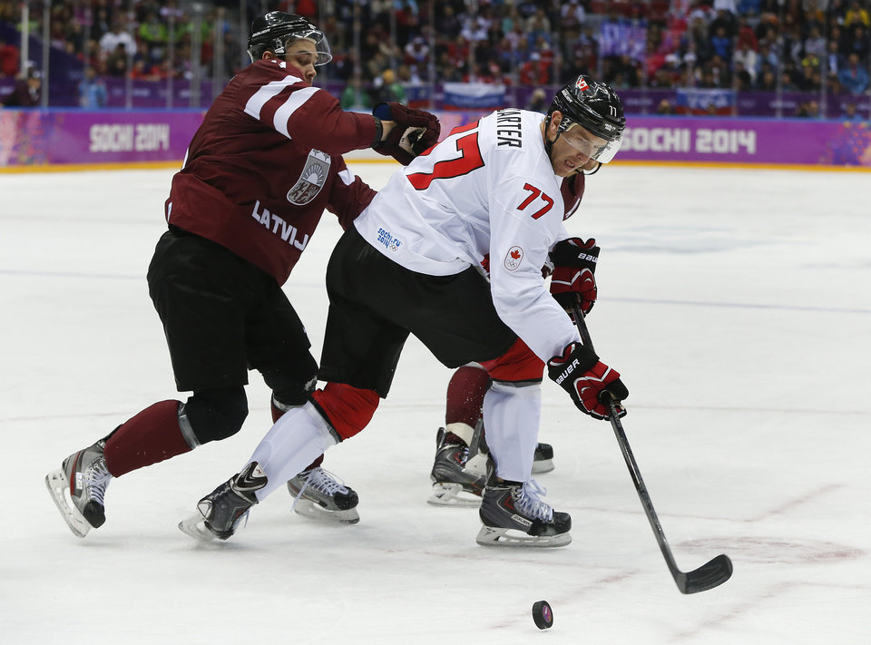 Photo - Latvia defenseman Kristaps Sotnieks pushes against Canada forward Jeff Carter during the second period of a men's quarterfinal ice hockey game at the 2014 Winter Olympics, Wednesday, Feb. 19, 2014, in Sochi, Russia. (AP Photo/Julio Cortez)